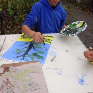 boy painting autumn trees