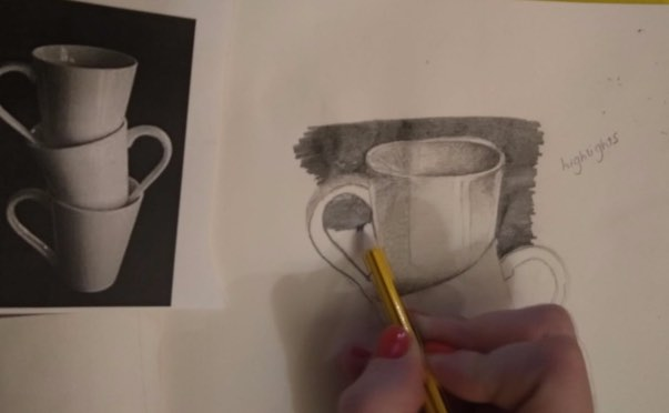 three cups and an artist sketching them with a pencil