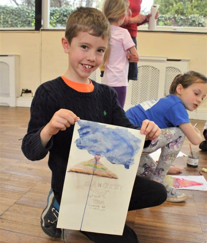 boy holding up painting