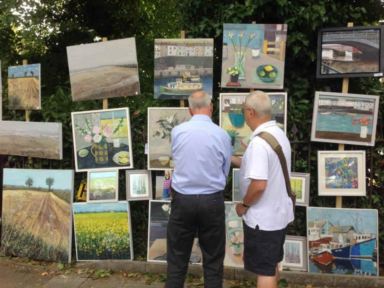 two men looking at art outside