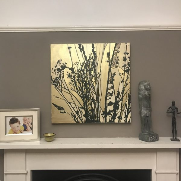 An abstract botanical gold painting glowing on a wall