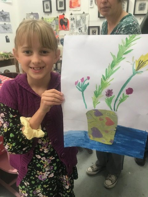 girl holding up a drawing of a flower