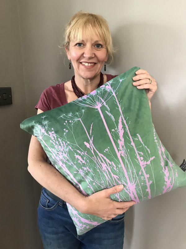 Jo Sharpe holding her pink and green botanical cushion